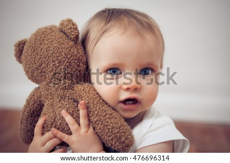 baby girl cuddling with a teddy bear