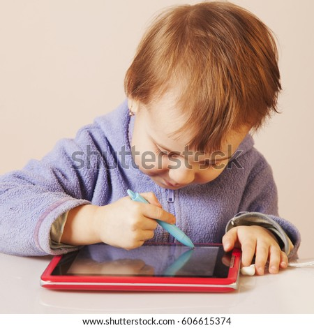 Baby girl drawing on the  graphics tablet. The young art and web designer. (Humorous picture)