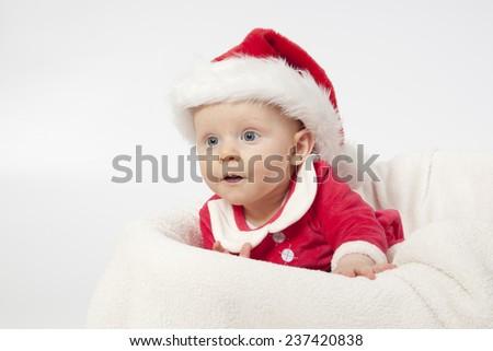 Baby girl dressed as santa on white background - stock photo