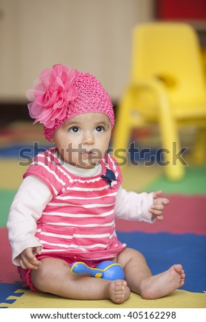 Baby girl dressed in pink with a rumba shaker