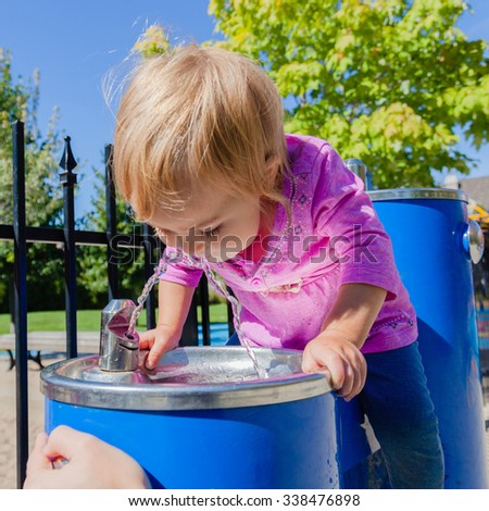 Baby girl drinking from water drinking fountain. Bright sun, hard shadows. Selective focus on water stream and girls face. - stock photo