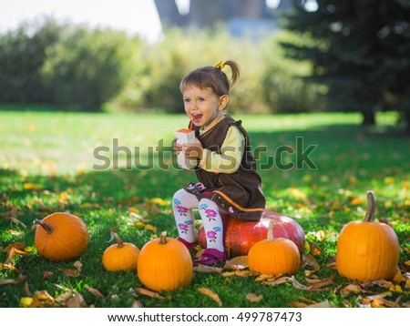 baby girl drinking juice in the autumn park with pumpkins