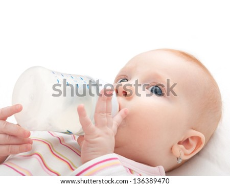Baby Girl Drinking Milk from Bottle on White Background - stock photo