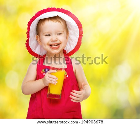 baby girl drinking orange juice in the summer outdoors - stock photo