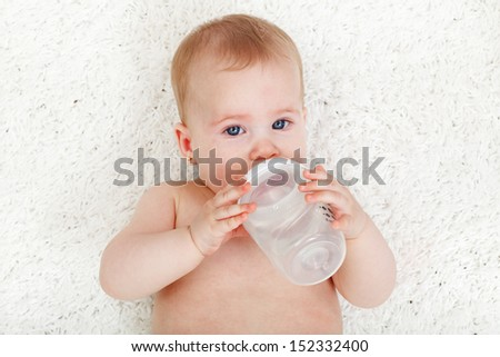 Baby girl drinking water from feeding bottle - laying on white rug - stock photo