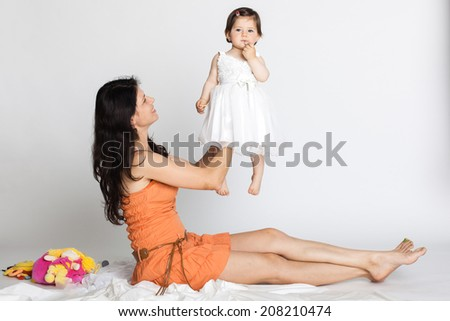 Baby girl eating a biscuit dressed in white isolated on white - stock photo