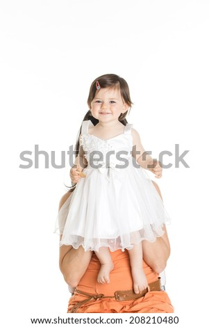 Baby girl eating a biscuit dressed in white standing on a chair - stock photo
