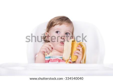 Baby girl eating banana, healthy food concept - stock photo