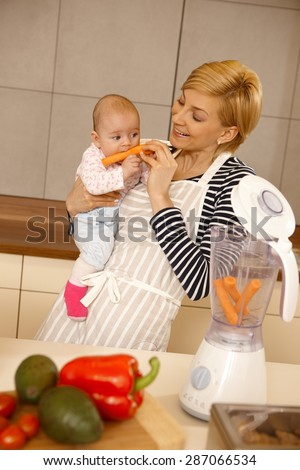 Baby girl eating carrot, mother holding her in arms in the kitchen. - stock photo