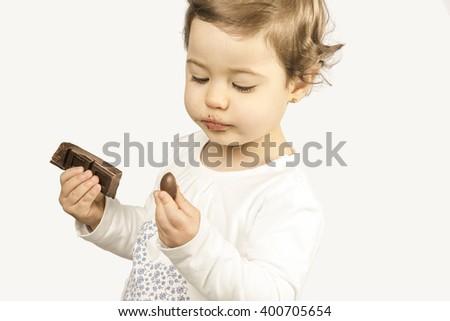 Baby girl eating chocolate - stock photo