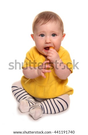 Baby girl eating finger food cutout - stock photo