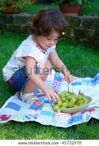 Baby girl eating green grapes on a pic-nic