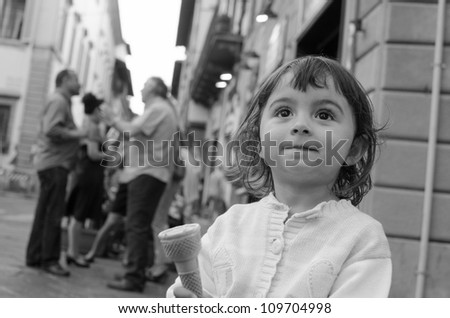 Baby girl eating Ice Cream in the City Streets, Italy - stock photo