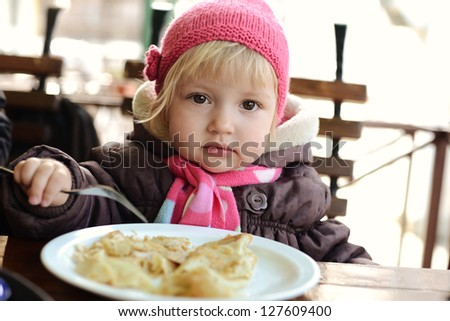 baby girl eating  in outdoor cafe - stock photo