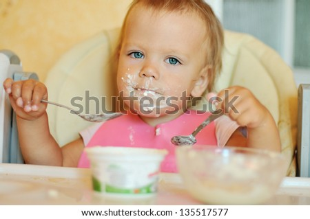 baby girl eating with two spoons