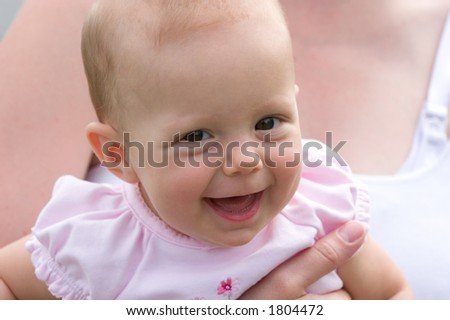 Baby girl filled with joy giving a big smile.