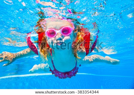 baby girl floating in the pool inflatable over-sleeves - stock photo