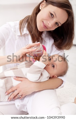 Baby girl held by her mother - drinking from nursing bottle - stock photo