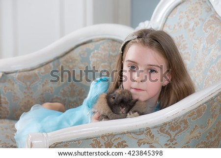 Baby girl holding a rabbit in the hands of - stock photo