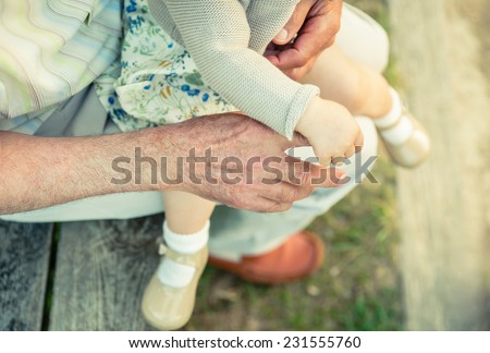Baby girl holding finger of senior man hand. Two different generations concept. - stock photo