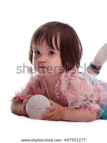 baby girl in a colorful dress isolated on a white background playing with a white ball