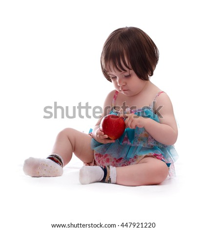 baby girl in a colorful dress isolated on a white background playing with red apple