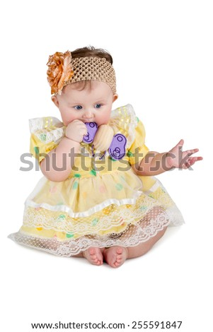 Baby girl in a dress and sling with a bow on head sitting and munches wooden toy isolated on white background