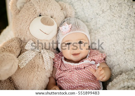 Baby girl in a lace hat with a flower smiling sitting on a fluffy rug