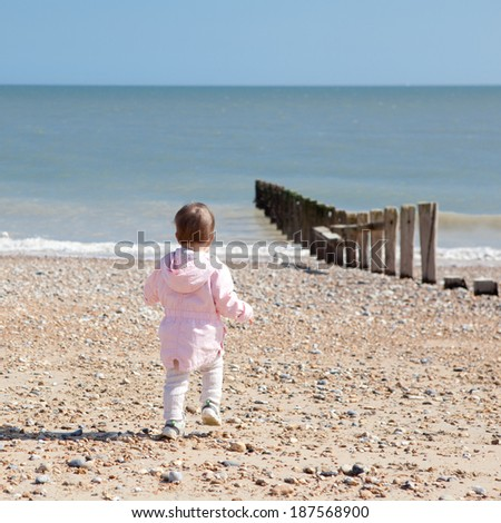 Baby girl in a pink coat on the beach running towards the sea - stock photo