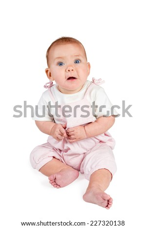 Baby girl in a white T-shirt and pink overalls sits with her mouth open and looking at camera isolated on white background - stock photo