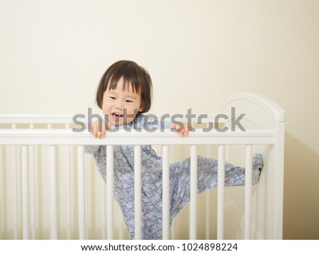baby girl in cot bed