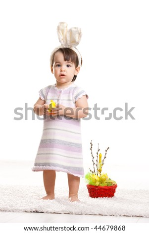 Baby girl in easter bunny costume, standing beside easter basket and holding toy chicken, looking amazed. Isolated on white background.