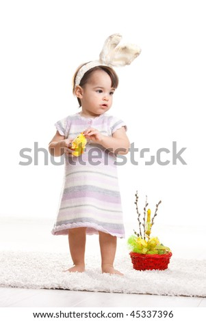 Baby girl in easter bunny costume, standing beside easter basket and playing with toy chicken. Isolated on white background.