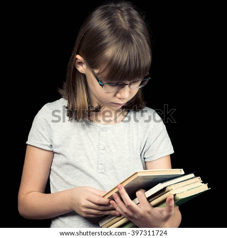 baby girl in glasses with book on dark background