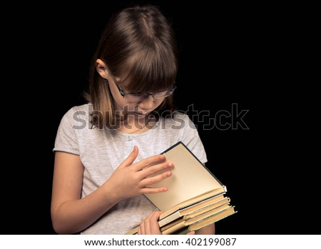 baby girl in glasses with book on the dark background