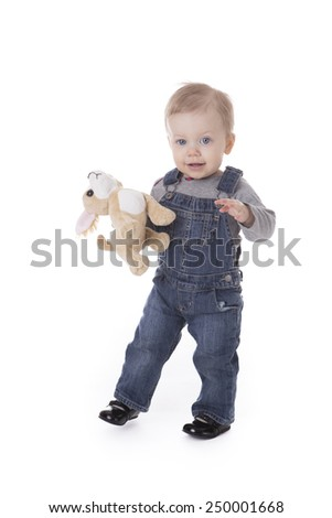 Baby girl in overalls holding puppy toy isolated on white - stock photo