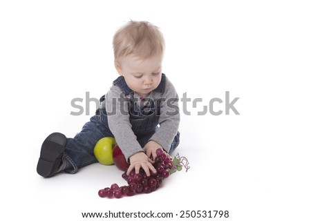 Baby girl in overalls playing with fruits isolated on white