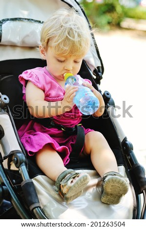 baby girl in pram with bottle of water - stock photo