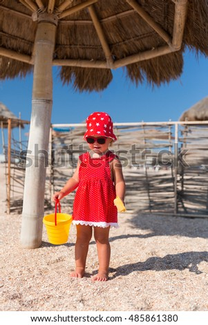 Baby girl in red dress and hat playing toys on a beach