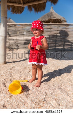 Baby girl in red dress and hat wearing sunglasses on a beach