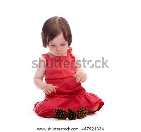 baby girl in red dress isolated on a white background playing with cones  - stock photo