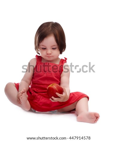 baby girl in red dress isolated on a white background playing with red apple - stock photo