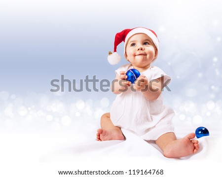 Baby girl in santa's hat with blue ornament balls sitting over light blue background - stock photo