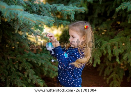baby girl in spring park decorated Christmas tree decorations Easter - stock photo