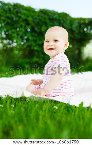 baby girl in striped dress sitting on green grass outdoors and smiling - stock photo