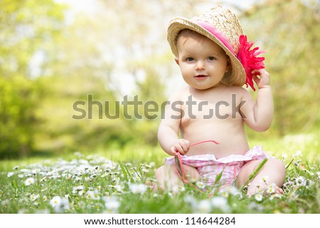 Baby Girl In Summer Dress Sitting In Field Wearing Sunglasses And Straw Hat - stock photo
