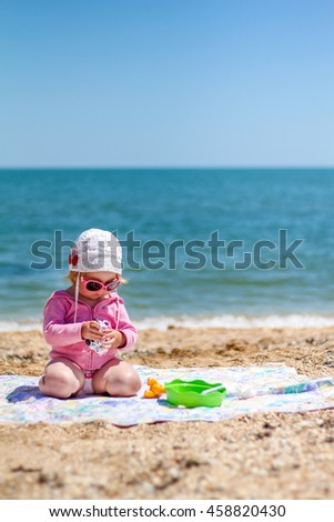 Baby girl in sunglasses playing on the beach near the sea on a hot day during the summer holidays
