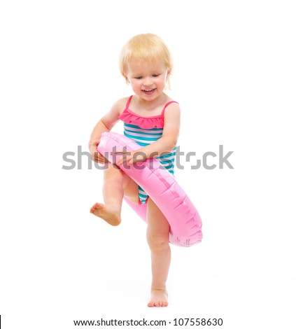 Baby girl in swimsuit playing with inflatable ring - stock photo