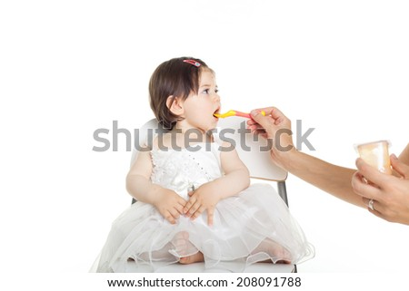 baby girl in white dress isolated on white background eating - stock photo