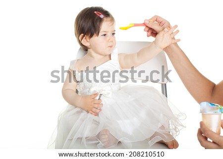 baby girl in white dress isolated on white background rejecting food - stock photo